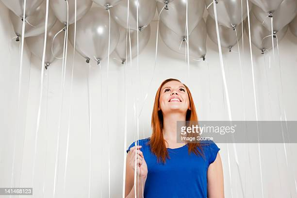 Young woman looking up at balloons