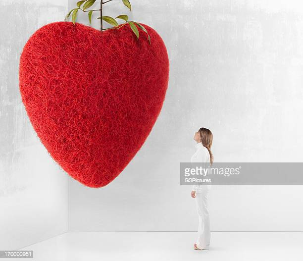 Young woman looking up at giant red felt heart