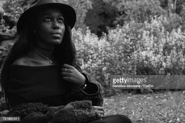 Young Woman Looking Up At Grassy Field