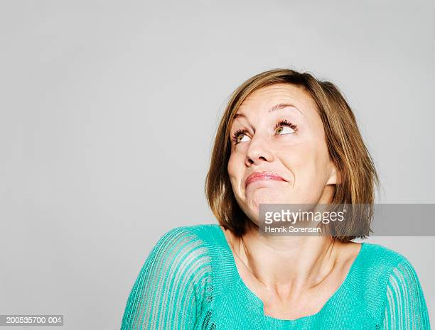 Young woman looking up, shrugging shoulders