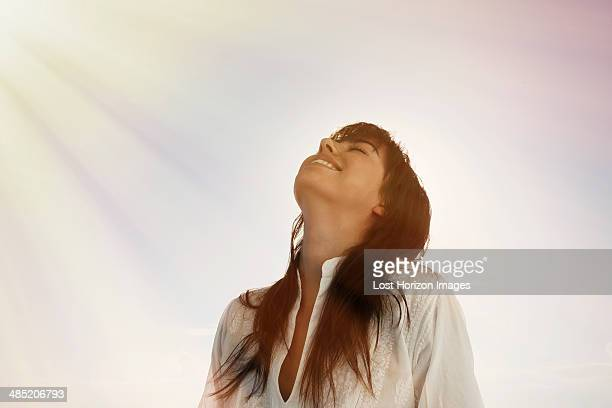 Young woman looking up, sun beams on face