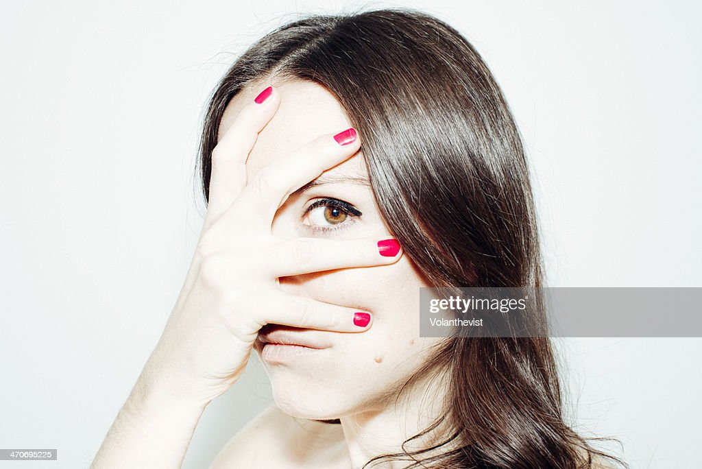 Young woman looking w/ one eye between the fingers : Stock Photo