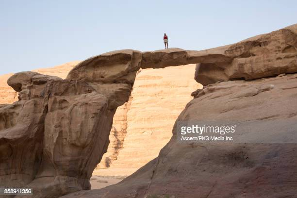 Young woman looks across desert landscape from natural arch