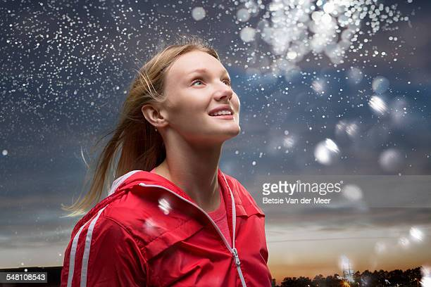 Young woman looks at star dust  in sky.