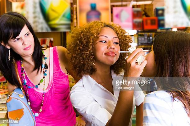 Young woman looks disapprovingly at friend getting makeover