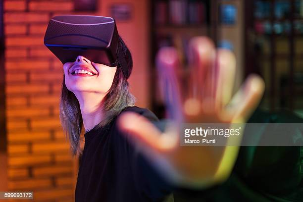 Young woman looks fascinated into Virtual Reality Headset