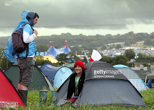 A young woman looks from inside her tent after pitching their campsite for the annual Glastonbury festival near Glastonbury Somerset on June 22 2011...