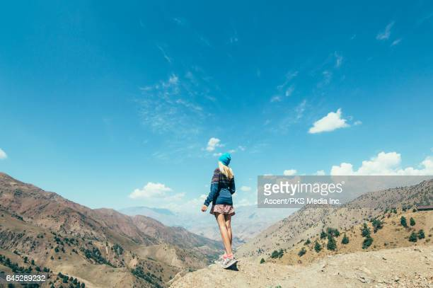 Young woman looks off from mountain slope, to landscape