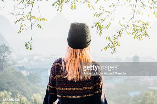 Young woman looks out across hazy village scene