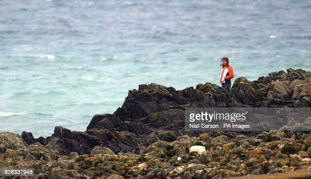 A young woman looks out at salvage experts Monday February 6th 2006 as they attempt to retrieve the wreck of the Rising Sun fishing boat which sank...