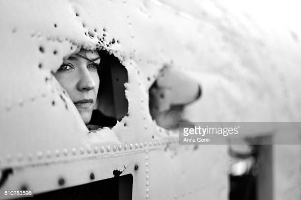 Young woman looks through bullet hole-ridden gap in battered plane wreck, black and white