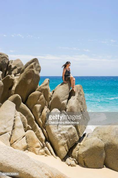 Young woman lounging on the rock formations around the Arch in Cabo San Lucas, Mexico.