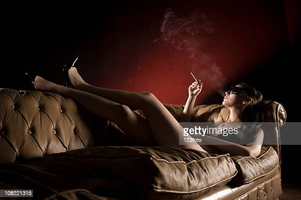 Young Woman Lounging With Feet Up on Couch Smoking Cigar