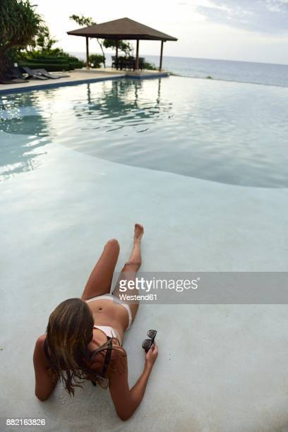 Young woman lying at swimming pool