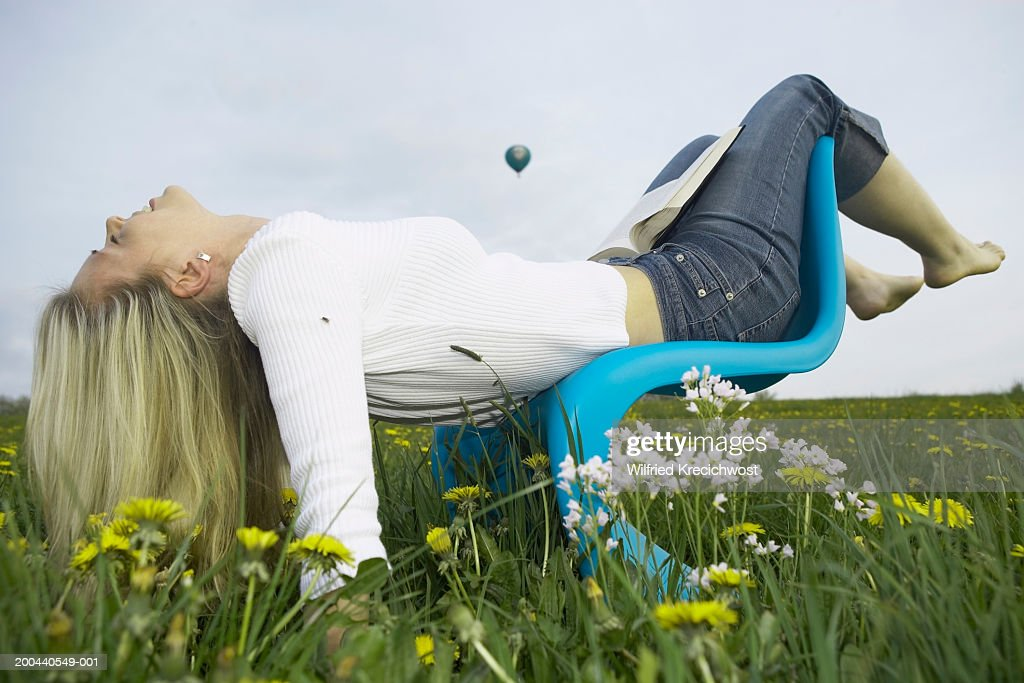 Young Woman Lying Backwards On Chair In Meadow, Hot Air Balloon In Sky :  Stock