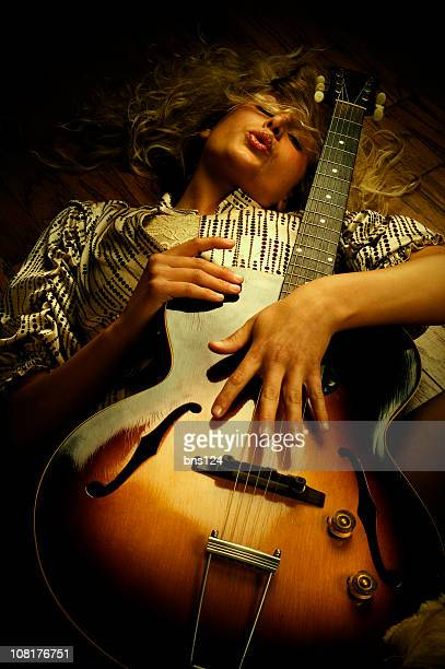 Young Woman Lying Down and Holding Vintage Guitar