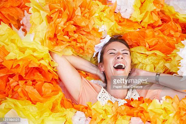 young woman lying down in giant paper pom poms