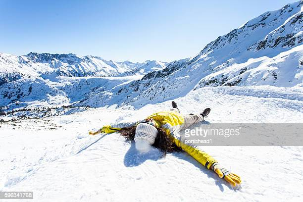 Young woman lying down on the snow
