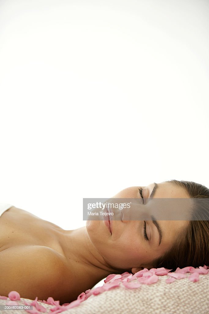 Young woman lying down with towel around body, eyes closed : Stock Photo