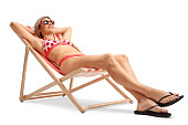 Young woman lying in a deck chair isolated on white background