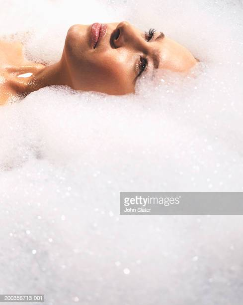 Young woman lying in bath surrounded by soap suds, close-up
