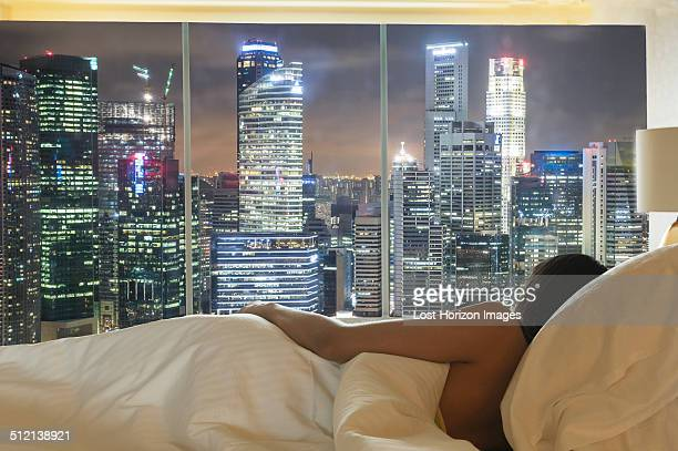 Young woman lying in bed looking at city skyline through window