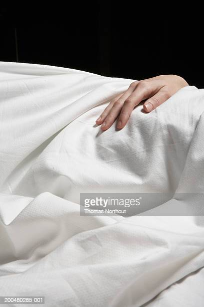 Young woman lying in bed, mid section (focus on hand atop sheet)