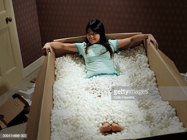 Young woman lying in carton covered with packing insulation