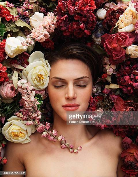 Young woman lying in flowers, eyes closed, overhead view