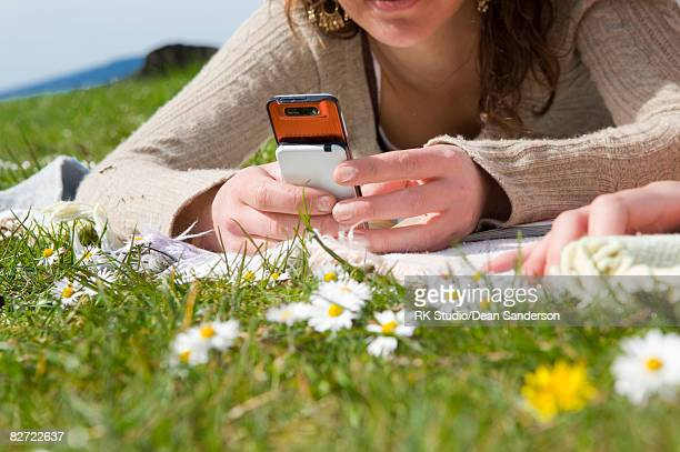 young woman lying in grass playing with cell phone