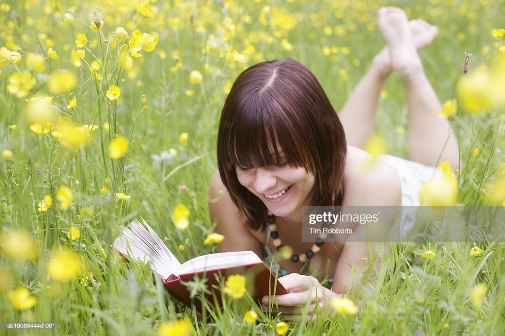 Young woman lying in grass reading book : Stock Photo