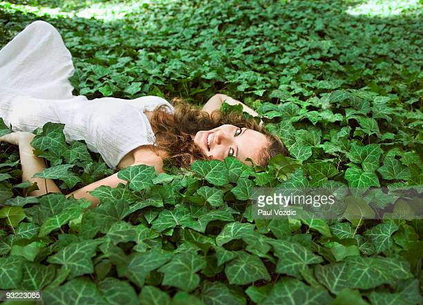 Young woman lying in ivy, smiling