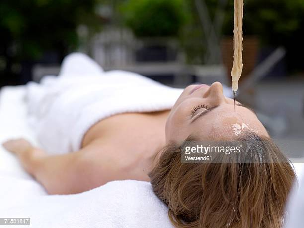 Young woman lying in spa with oil being poured on forehead, eyes closed