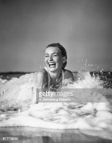 Young woman lying in surf, laughing. : Stock Photo