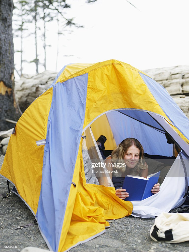 Young woman lying in tent, reading book