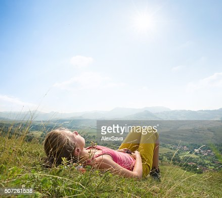 Giovane donna sdraiata nell'erba