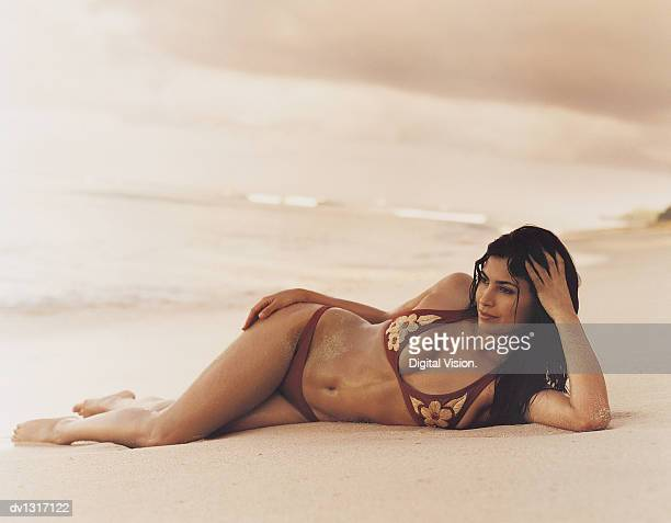 Young Woman Lying on a Beach Wearing a Bikini