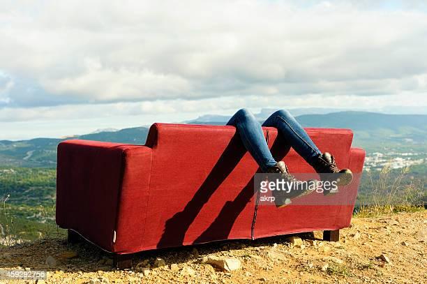 Jeune femme allongée sur un canapé en plein air