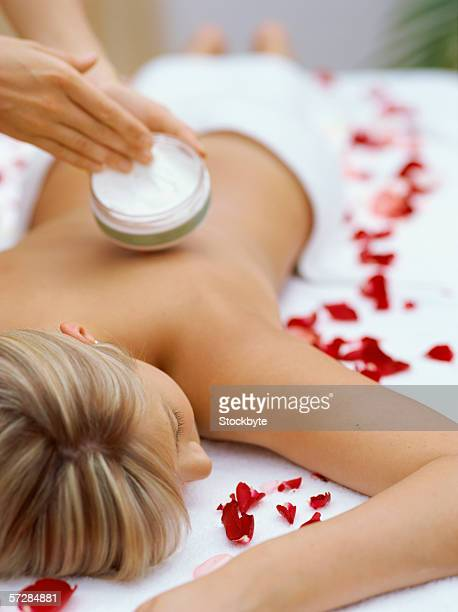 Young woman lying on a massage table with another woman holding moisturizer