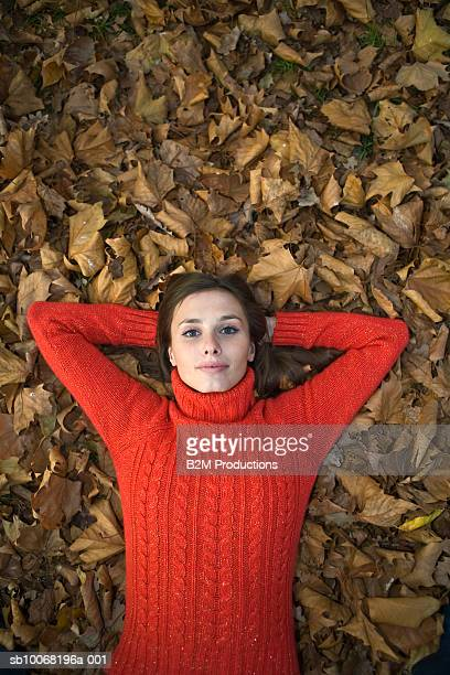 Young woman lying on autumn leaves, portrait