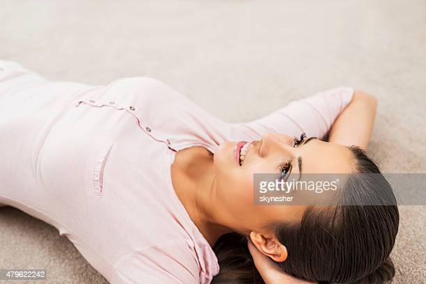 Young woman lying on back and day dreaming.