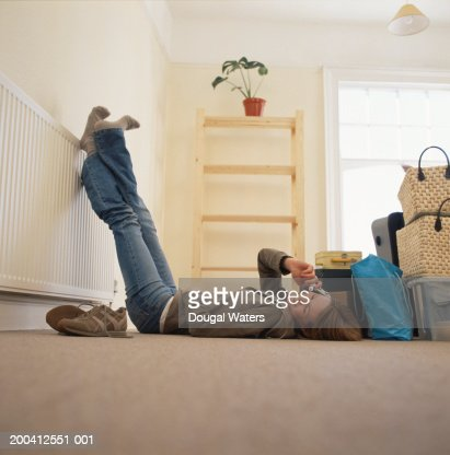 Young woman lying on back with feet on radiator using mobile