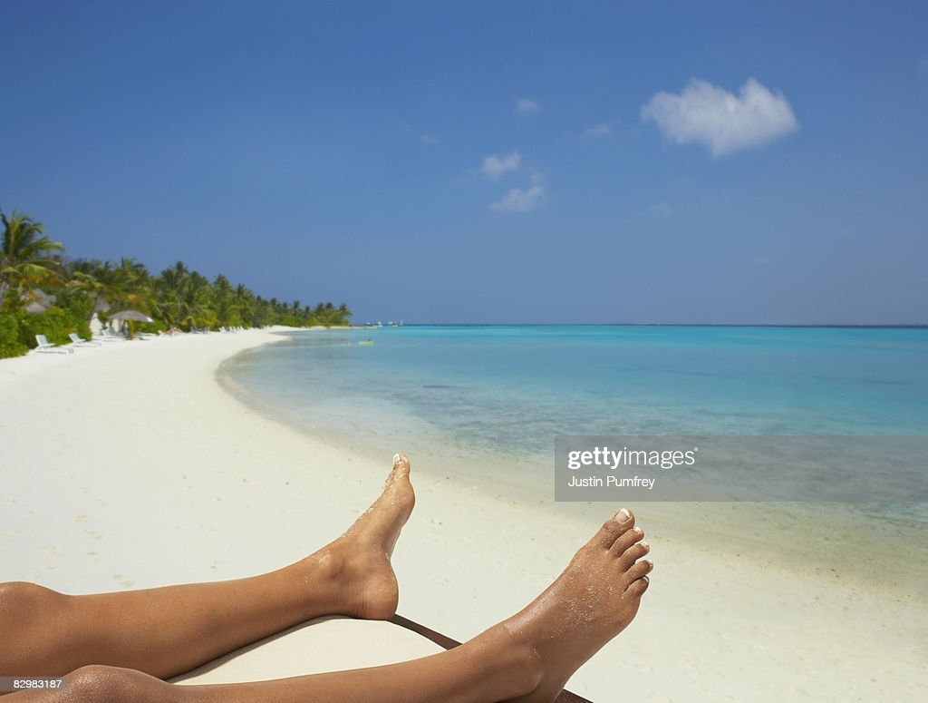 Young woman lying on beach, legs only : Stock Photo