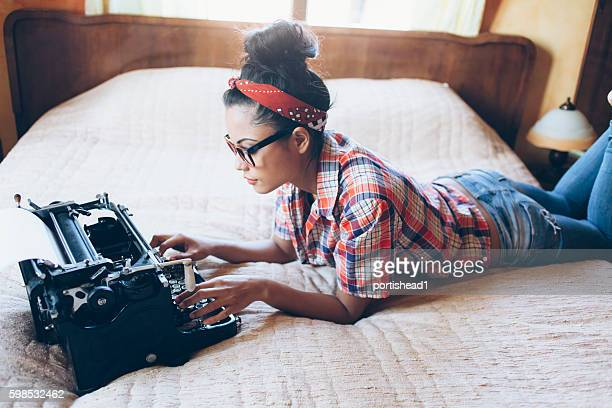 Young woman lying on bed and writing on vintage typewriter