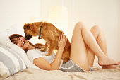 Young woman lying on bed having face licked by pet dog