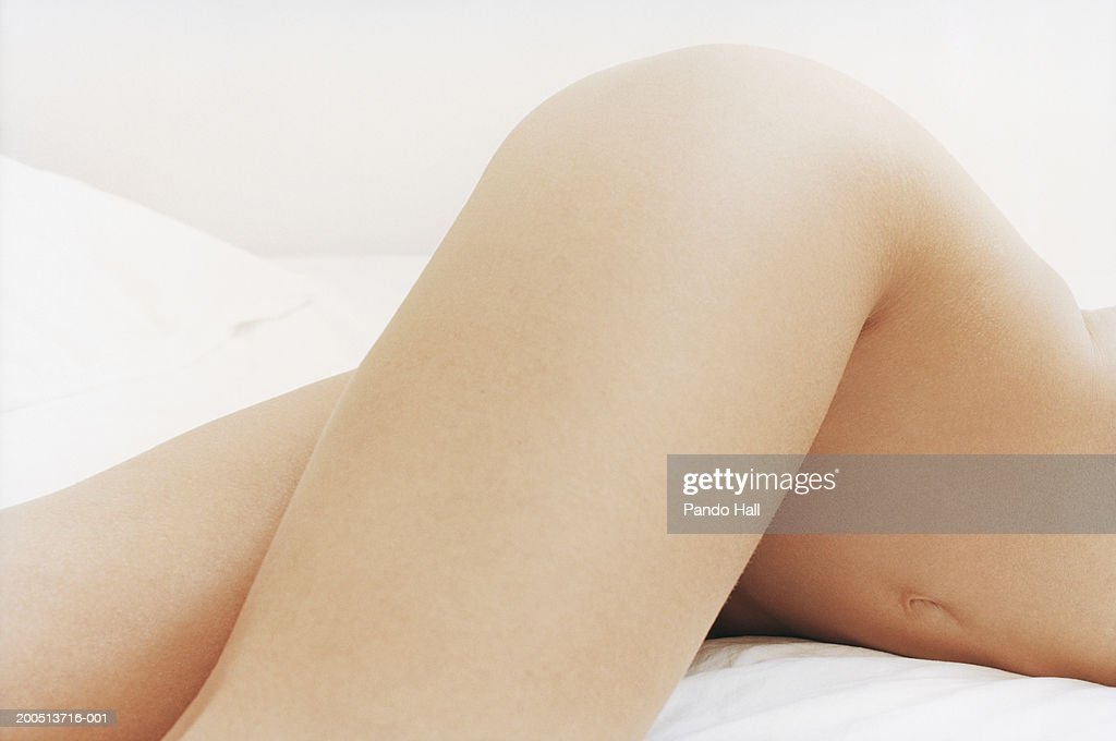 Young woman lying on bed, naked, mid section : Stock Photo