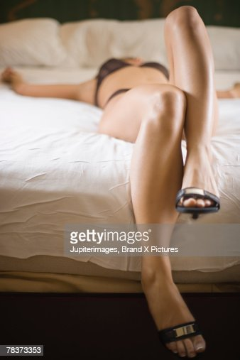 Young woman lying on bed : Stock Photo