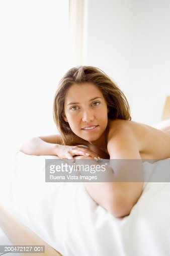 Young woman lying on bed, portrait : Stock Photo