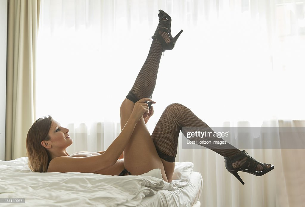 Young woman lying on bed putting on fishnet stockings : Stock Photo