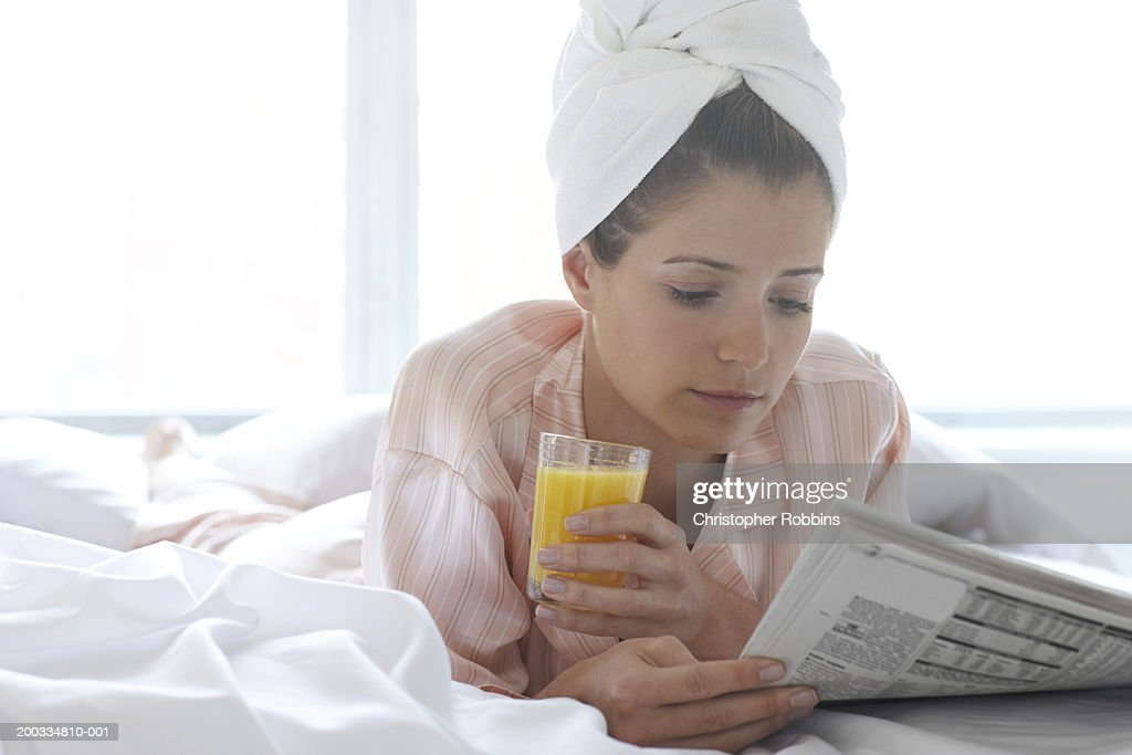 Young woman lying on bed reading newspaper, towel around head : Stock Photo